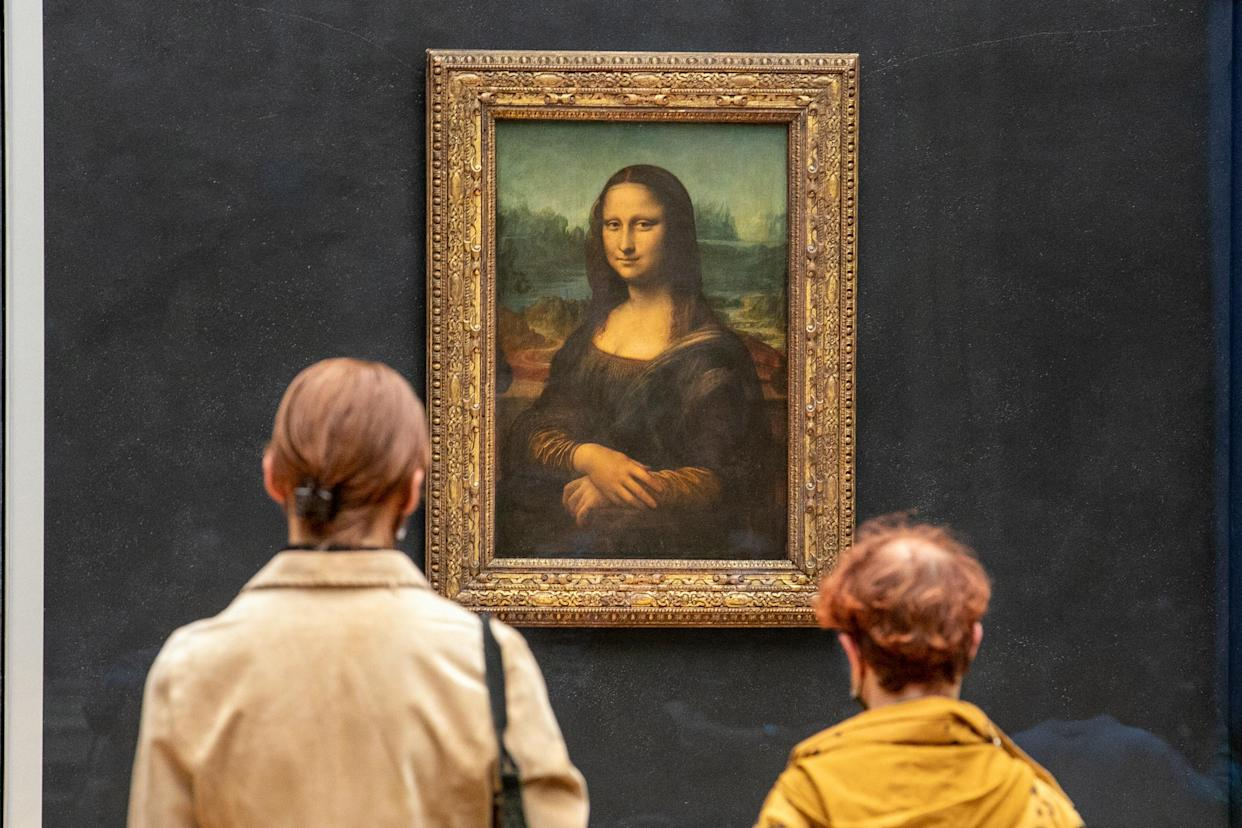 PARIS, FRANCE - MAY 19: Visitors observe the painting 'La Joconde' The Mona Lisa by Italian artist Leonardo Da Vinci on display in a gallery at Louvre on May 19, 2021 in Paris, France. The country is taking steps to ease the lockdown measures that President Emmanuel Macron announced on April 29, allowing all the museums and non-essential shops and cultural venues to open and rolling back the curfew to 9pm. The cafe and restaurant terraces can also open to 50% capacity. France is reporting a seven-day average of around 14,000 new Covid-19 cases. (Photo by Marc Piasecki/Getty Images)