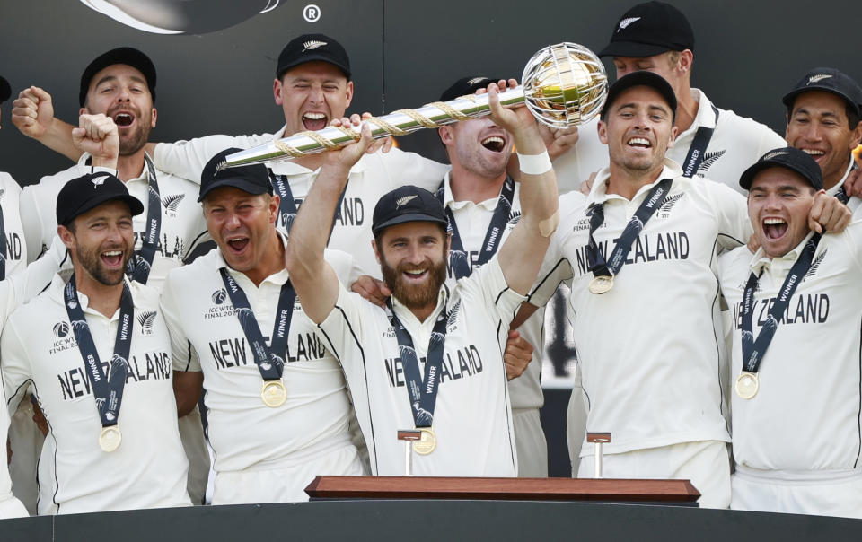 Cricket - ICC World Test Championship Final - India v New Zealand - Rose Bowl, Southampton, Britain - June 23, 2021 New Zealand's Kane Williamson celebrates with the trophy and teammates after winning the final to because the ICC World Test Champions