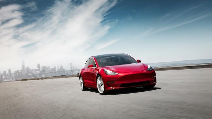 A red Tesla Model 3 with a cityscape in the background.