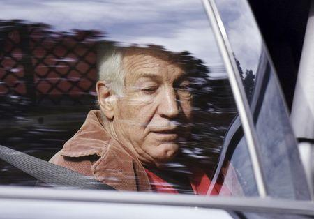 Convicted child molester Jerry Sandusky, a former assistant football coach at Penn State University, is seen in the back seat of a sheriff's vehicle after his appeal hearing at the Centre County Courthouse in Bellefonte, Pennsylvania