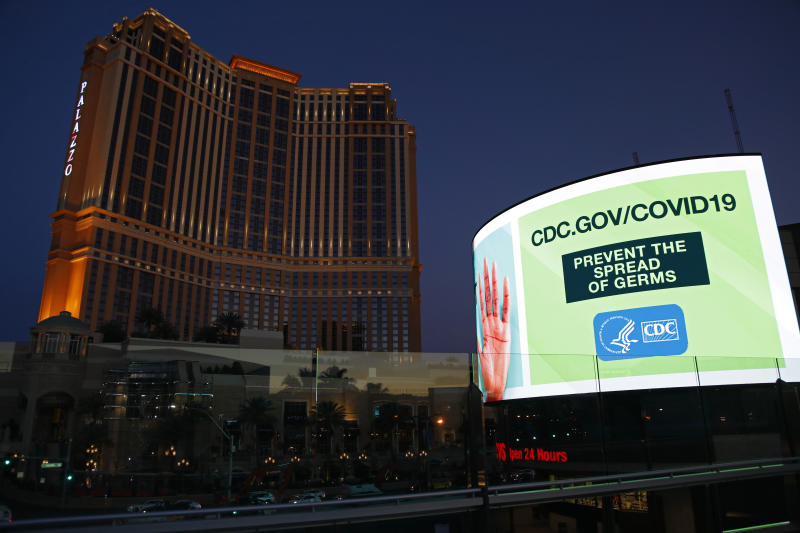 A sign advises people to minimized the spread of germs, along the Las Vegas Strip devoid of the usual crowds during the coronavirus outbreak Tuesday, May 26, 2020, in Las Vegas. (AP Photo/John Locher)