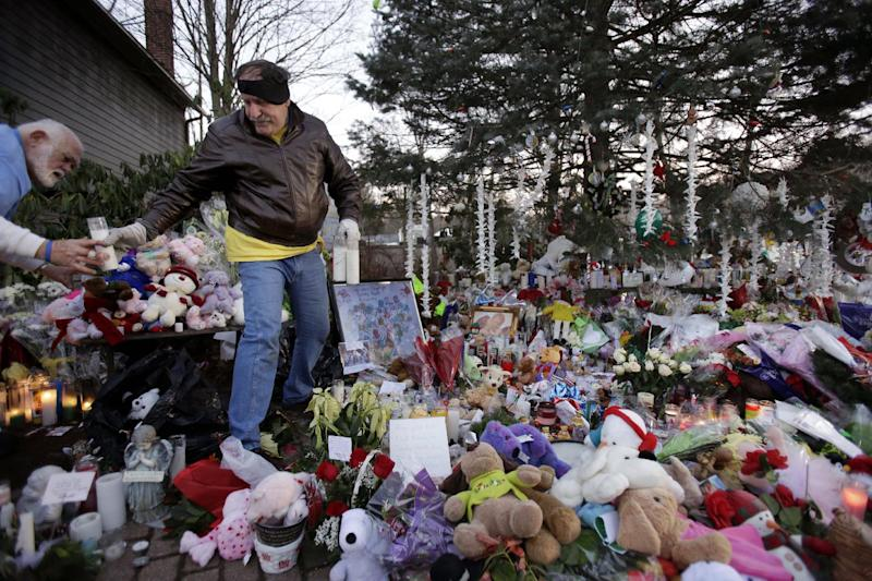 Herb Pontow, left, and Tony Tipton, both from Maryland, try to clean and organize an overflowing memorial to the shooting victims in the Sandy Hook village of Newtown, Conn., Thursday, Dec. 20, 2012. Adam Lanza walked into Sandy Hook Elementary School in Newtown, Dec. 14, and opened fire, killing 26 people, including 20 children, before killing himself. (AP Photo/Seth Wenig)