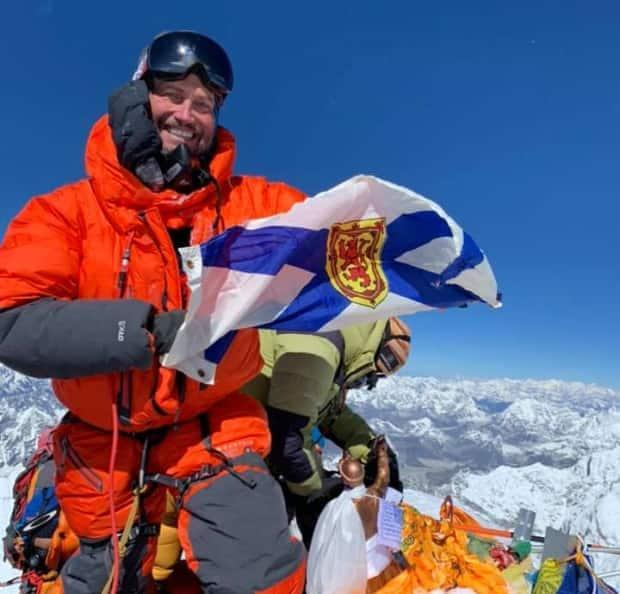 Kevin Walsh of Falmouth, N.S., holds the provincial flag at the summit of Mount Everest. (Everest training/Facebook - image credit)