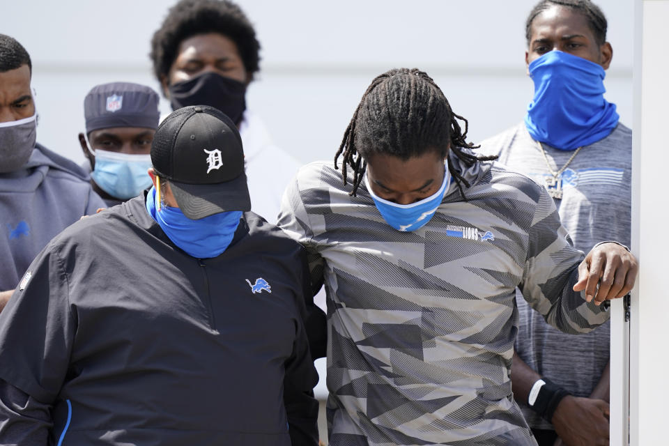 Matt Patricia, left, and Lions player listen with bowed heads during their statement to the media after canceling practice in August after the police shooting of Jacob Blake.