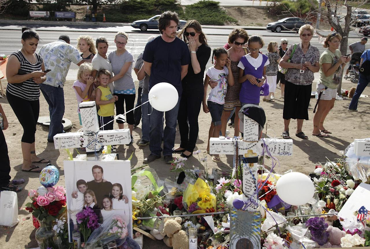 """Actor Christian Bale, center, left, and his wife Sibi Blazic visit a memorial to the victims of Friday's mass shooting, Tuesday, July 24, 2012, in Aurora, Colo. Twelve people were killed when a gunman opened fire during a late-night showing of the movie """"The Dark Knight Rises,"""" which stars Bale as Batman. (AP Photo/Ted S. Warren)"""