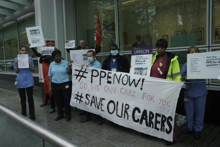 Hospital workers take part in a protest calling on the British government to provide PPE (personal protective equipment) across Britain for all workers in care, the NHS (National Health Service) and other vital public services after a nationwide minute's silence to remember medical staff and key workers that have died from the coronavirus, at University College Hospital in London, Tuesday, April 28, 2020. One of the protesters stressed the point that their hospital Trust has good levels of PPE and that they want the government to provide more PPE to people elsewhere that don't have enough. (AP Photo/Matt Dunham)