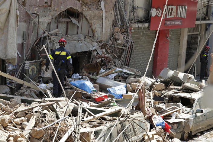 "A French fireman and a rescue dog search in the rubble of a building after the Tuesday explosion at the seaport of Beirut, in Beirut, Lebanon, Thursday, Aug. 6, 2020. Lebanese officials targeted in the investigation of the massive blast that tore through Beirut sought to shift blame for the presence of explosives at the city's port, and the visiting French president warned that without serious reforms the country would ""continue to sink."" (AP Photo/Hassan Ammar)"