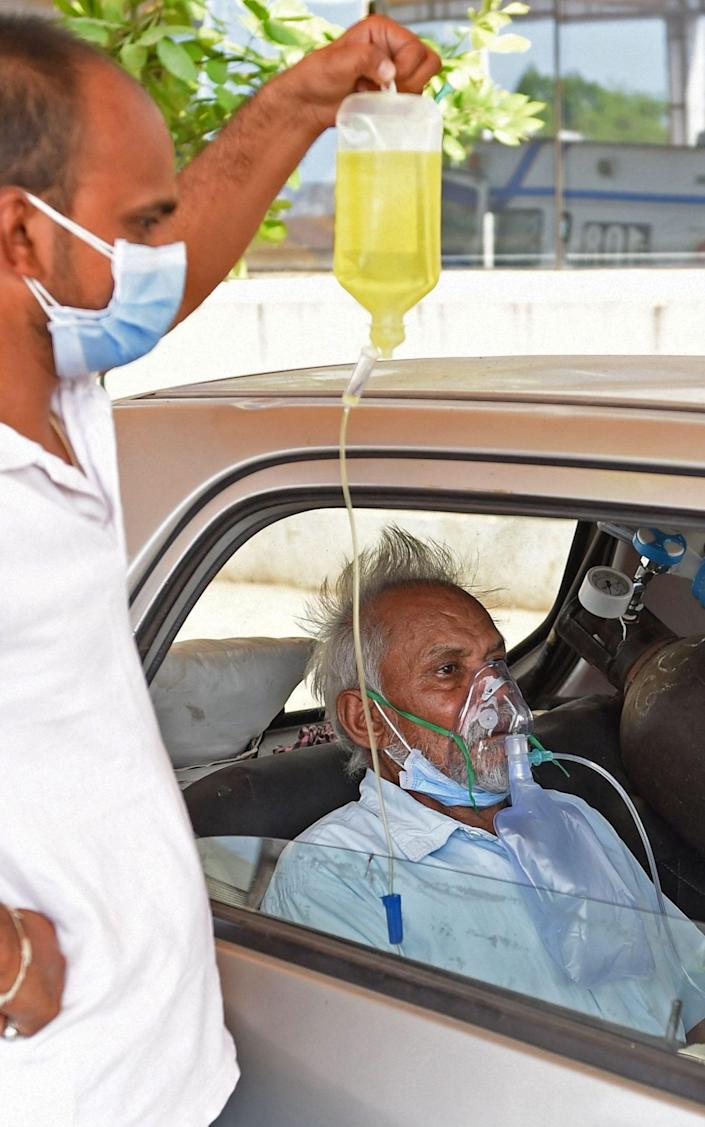 A Covid-19 coronavirus patient on oxygen support sits inside a car while waiting for admission in a civil hospital in Ahmedabad - Sam Panthaky/AFP