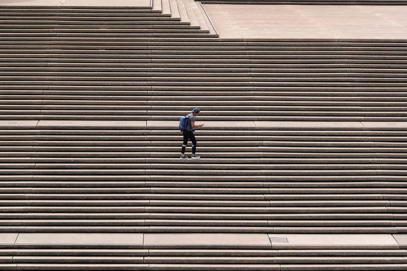 A lone man stands on the steps of the Sydney Opera House in Sydney