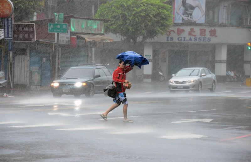 A man walks in rain brought by Typhoon Matmo in Xindien district in New Taipei City on July 23, 2014