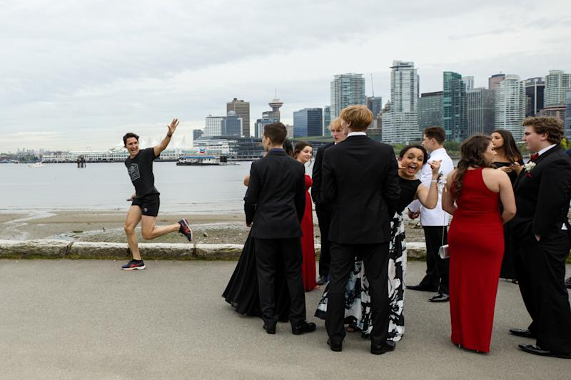 Prime Minister Justin Trudeau jogs past a group of high school students dressed for their prom in Vancouver, British Columbia, Canada on May 19, 2017. Picture taken on May 19, 2017. Adam Scotti/Courtesy Prime Minister's Office/Handout via REUTERS ATTENTION EDITORS - THIS IMAGE WAS PROVIDED BY A THIRD PARTY. EDITORIAL USE ONLY. TPX IMAGES OF THE DAY