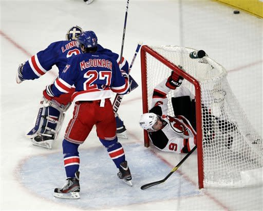 New Jersey Devils' Zach Parise, right, goes into the net after his shot was deflected by New York Rangers goalie Henrik Lundqvist, rear, of Sweden, and Ryan McDonagh (27) during the first period of Game 1 of their NHL hockey Stanley Cup Eastern Conference final playoff series, Monday, May 14, 2012, at New York's Madison Square Garden. (AP Photo/Julio Cortez)