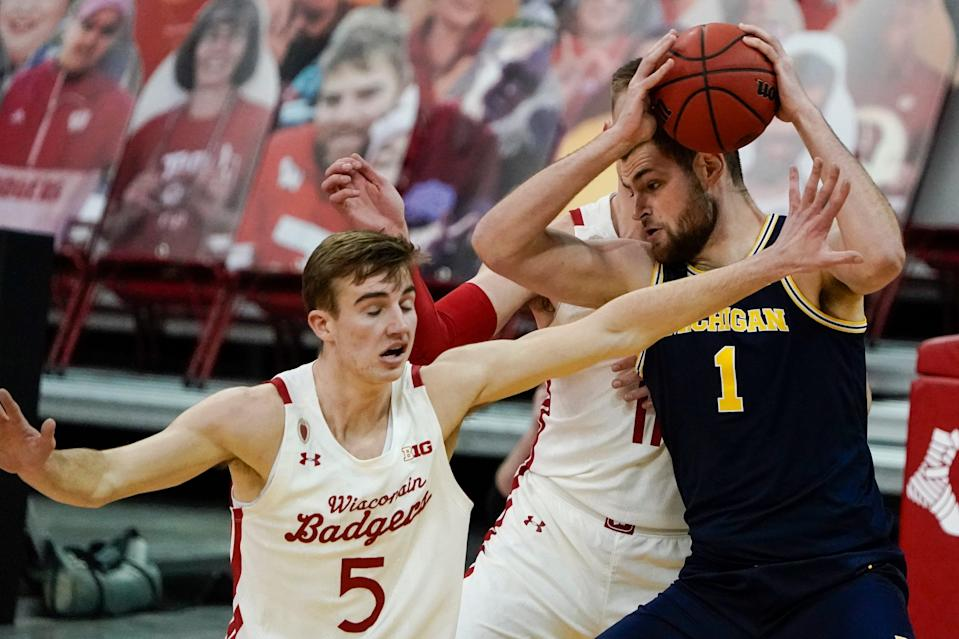 Michigan's Hunter Dickinson tries to get past Wisconsin's Tyler Wahl (5) and Micah Potter (11) during the first half of an NCAA college basketball game Sunday, Feb. 14, 2021, in Madison, Wis.