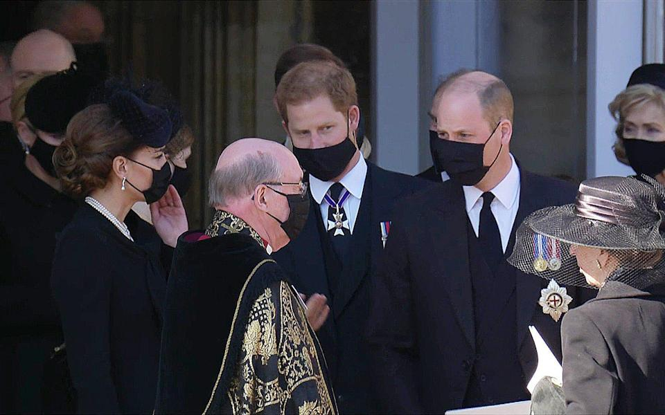 Kate with Harry and William as they talk to the Dean of Windsor after the funeral service  - Pixel