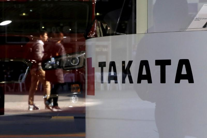 FILE PHOTO - A logo of Takata Corp is seen with its display as people are reflected in a window at a showroom for vehicles in Tokyo