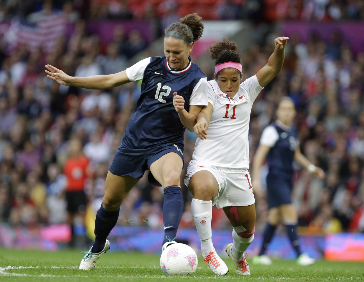Canada's Desiree Scott, right, battles for the ball against the United States' Lauren Cheney, left, during their semifinal women's soccer match at the 2012 London Summer Olympics, in Manchester, England, Monday, Aug. 6, 2012. (AP Photo/Hussein Malla)