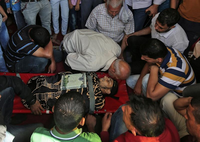 Palestinian mourners gather around the body of a man who was killed during a protest at the Israel-Gaza border on May 14, 2018, during his funeral at a mosque in Khan Yunis in the southern Gaza Strip