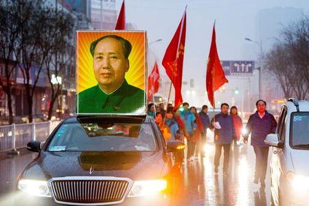 A picture of China's late Chairman Mao Zedong is seen on top of car as people gather to celebrate Mao's 123rd birth anniversary in Shaoshan