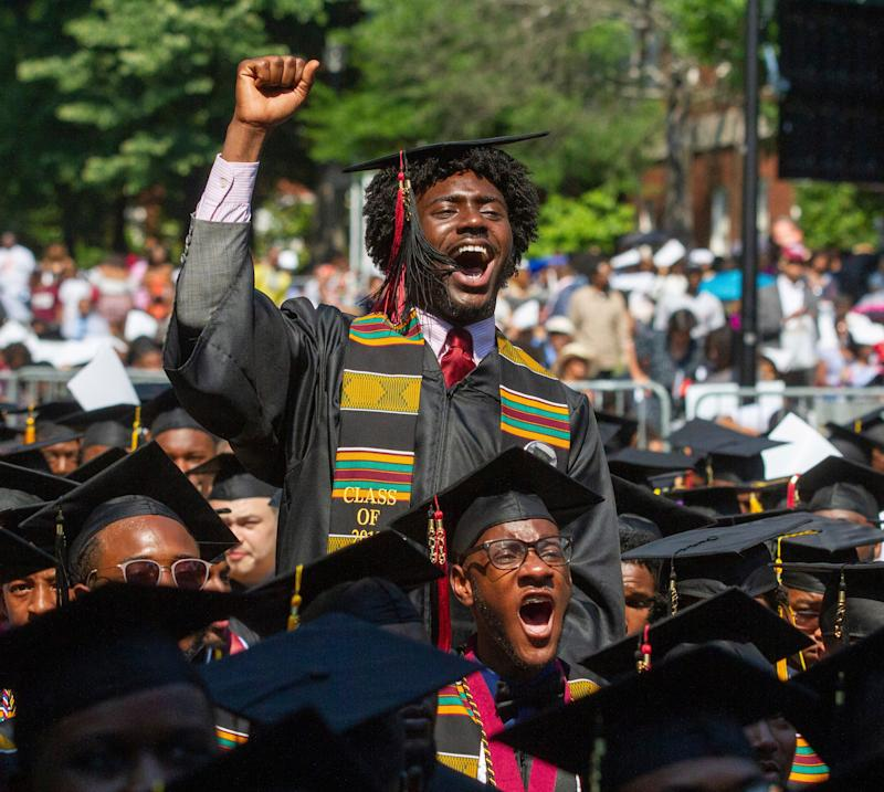 Graduates react after hearing billionaire technology investor and philanthropist Robert F. Smith say he will provide grants to wipe out the student debt of the entire 2019 graduating class at Morehouse College in Atlanta, Sunday, May 19, 2019. (Steve Schaefer/Atlanta Journal-Constitution via AP) ORG XMIT: GAATJ901
