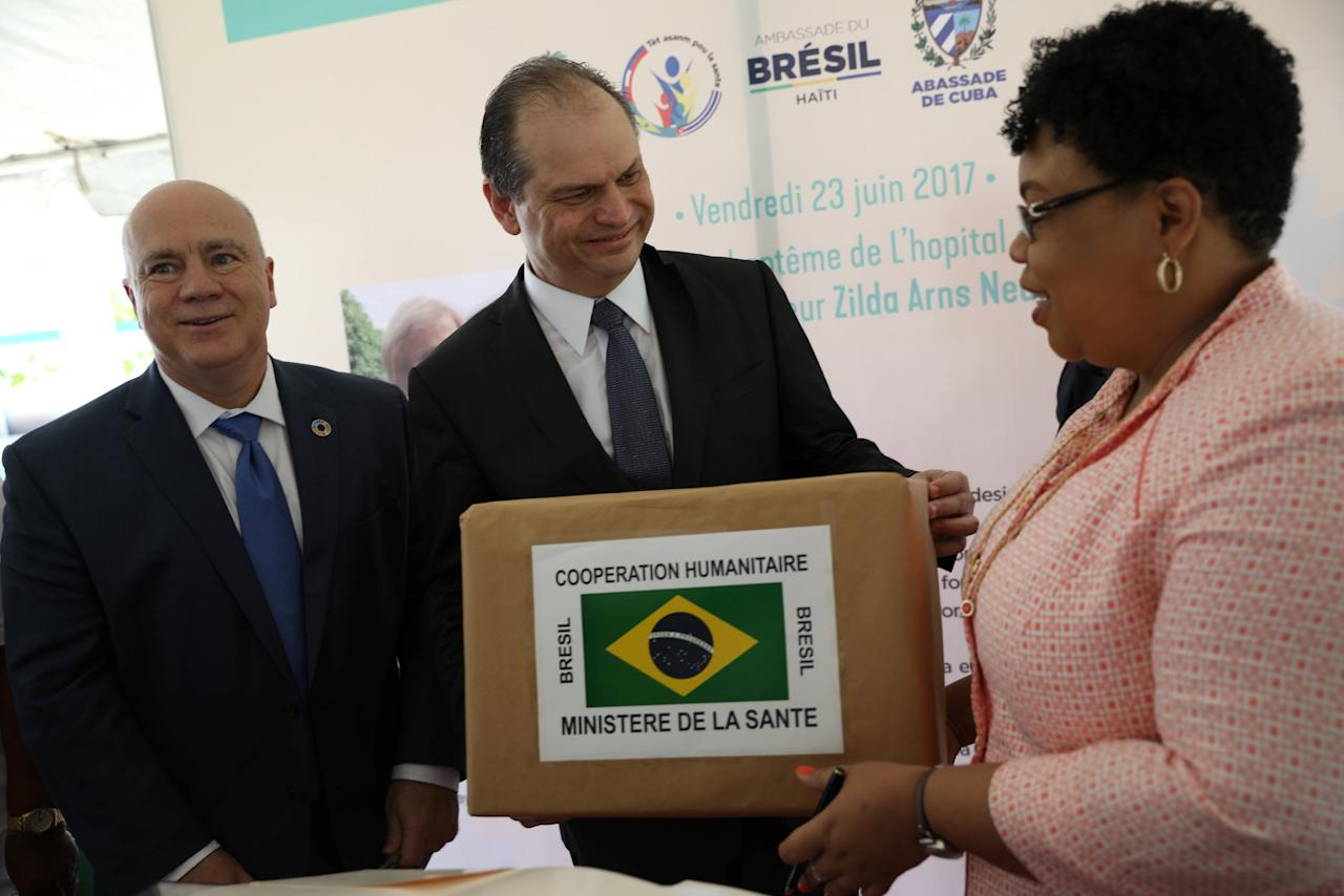 Haitian Minister of Public Health and Population Marie Greta Roy Clement (R) receives a symbolic donation from Brazilian Health Minister Ricardo Barros (C), in presence of United Nations Resident Coordinator in Brazil Niky Fabiancic, during a ceremony at Dr. Zilda Arns Hospital, on the outskirts of Port-au-Prince, Haiti, June 23, 2017. REUTERS/Andres Martinez Casares