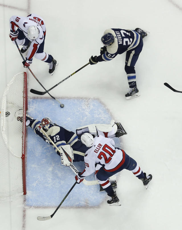 Columbus Blue Jackets' Sergei Bobrovsky (72), of Russia, makes a save as teammate Ryan Murray, top right, tries to clear the puck away from Washington Capitals' Nicklas Backstrom, top left, of Sweden, and Lars Eller, of Denmark, during the third period of an NHL hockey game Tuesday, Feb. 12, 2019, in Columbus, Ohio. The Blue Jackets beat the Capitals 3-0. (AP Photo/Jay LaPrete)