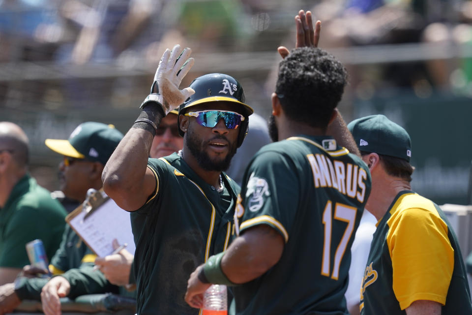 Oakland Athletics' Starling Marte, left, is congratulated by Elvis Andrus after scoring against the Seattle Mariners during the first inning of a baseball game in Oakland, Calif., Tuesday, Aug. 24, 2021. (AP Photo/Jeff Chiu)