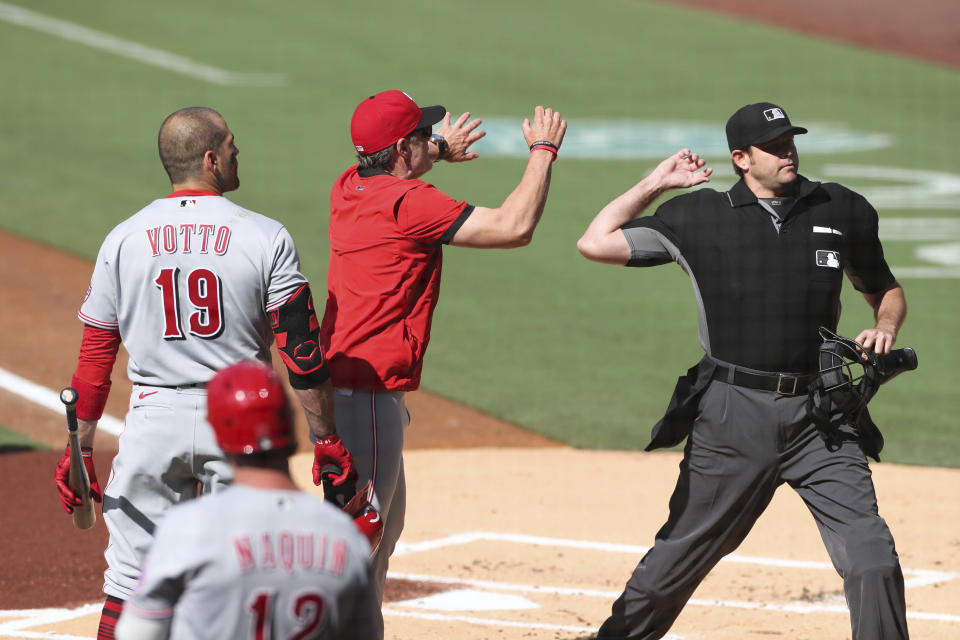 Joey Votto (19) and manager David Bell, center, of the Cincinnati Reds are ejected in the first inning following a heated argument with home plate umpire Ryan Additon, right, Saturday, June 19, 2021, in San Diego. (AP Photo/Derrick Tuskan)