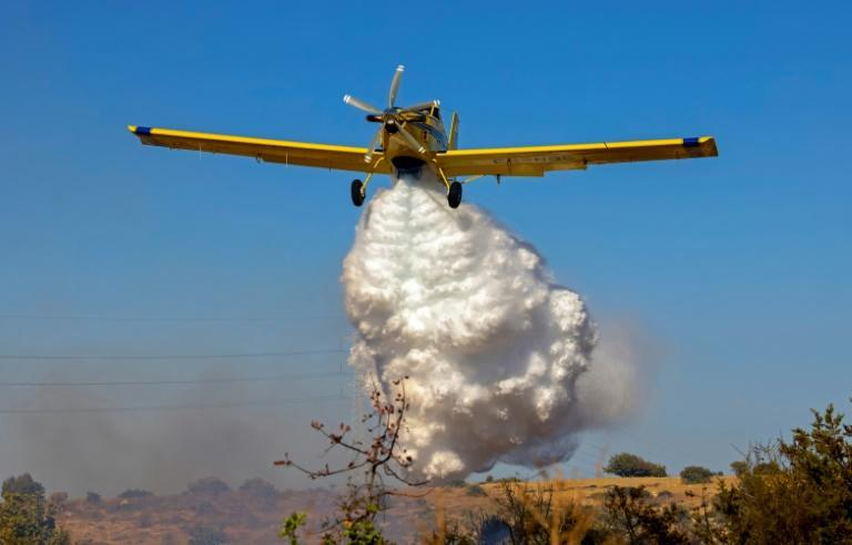A Spanish Air Tractor firefighting plane dumps water on the southern slopes of the Troodos mountains close to Agioi Vavatsinias village as a major fire continues to burn on the Mediterranean island of Cyprus on July 4, 2021