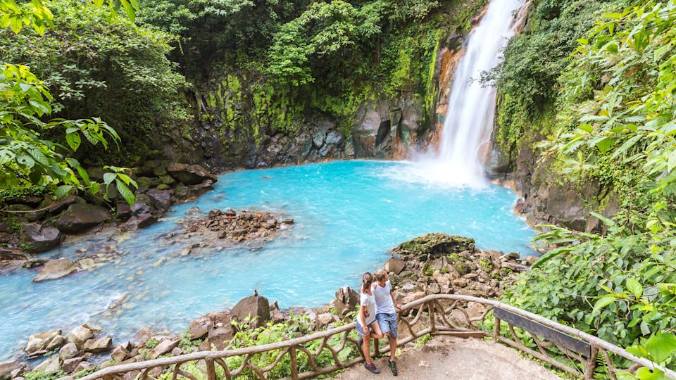 Tourist couple looking at Rio Celeste waterfall, Tenorio Volcano National Park, Guanacaste, Costa Rica.