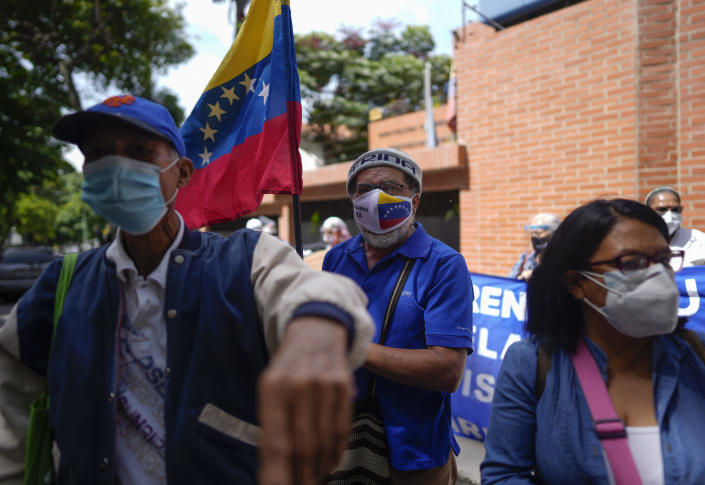 People gather outside the offices of the Pan American Health Organization and World Health Organization, during a small protest demanding COVID-19 vaccines be made available in Caracas, Venezuela, Thursday, Sept. 9, 2021. (AP Photo/Ariana Cubillos)