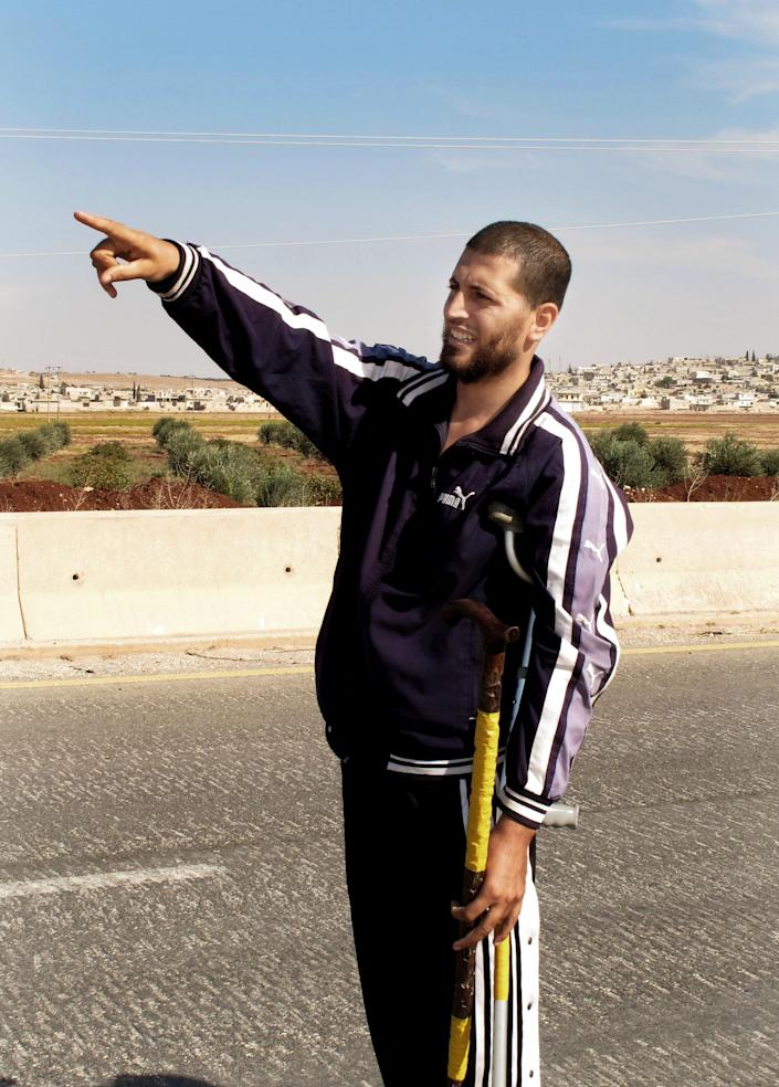 In this Wednesday, Oct. 17, 2012 photo, Free Syrian Army fighter, Bashar al Hajji, points towards the besieged Shiite village of Zahraa in Aleppo, Syria. Anyone who dares try to slip out of the Shiite villages of Zahraa and Nubl risks their lives. Snipers outside town are ready to gun them down. Roads out are blocked with barricades and checkpoints. Rebels have imposed a smothering siege over the communities, which they call a den of pro-regime gunmen who have shelled, killed and kidnapped neighboring Sunnis. (AP Photo/Rob Celliers)