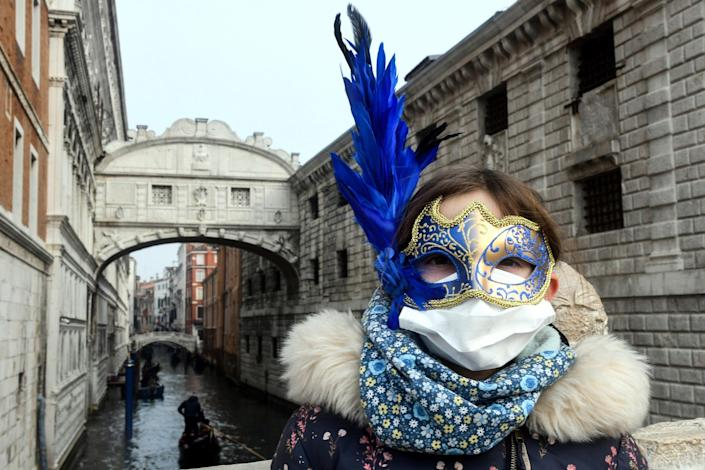 A young tourist wearing a protective facemask and a Carnival mask visits the streets of Venice, on February 24, 2020 during the usual period of the Carnival festivities which the last two days have been cancelled.