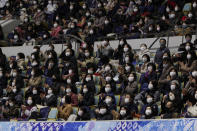Spectators wearing face masks looks towards an electric board for performance results during a free skating of an ISU Grand Prix of Figure Skating competition in Kadoma near Osaka, Japan, Saturday, Nov. 28, 2020. (AP Photo/Hiro Komae)