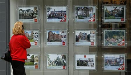 A woman looks at properties advertised for sale in the window of an estate agent in Hale, northern England