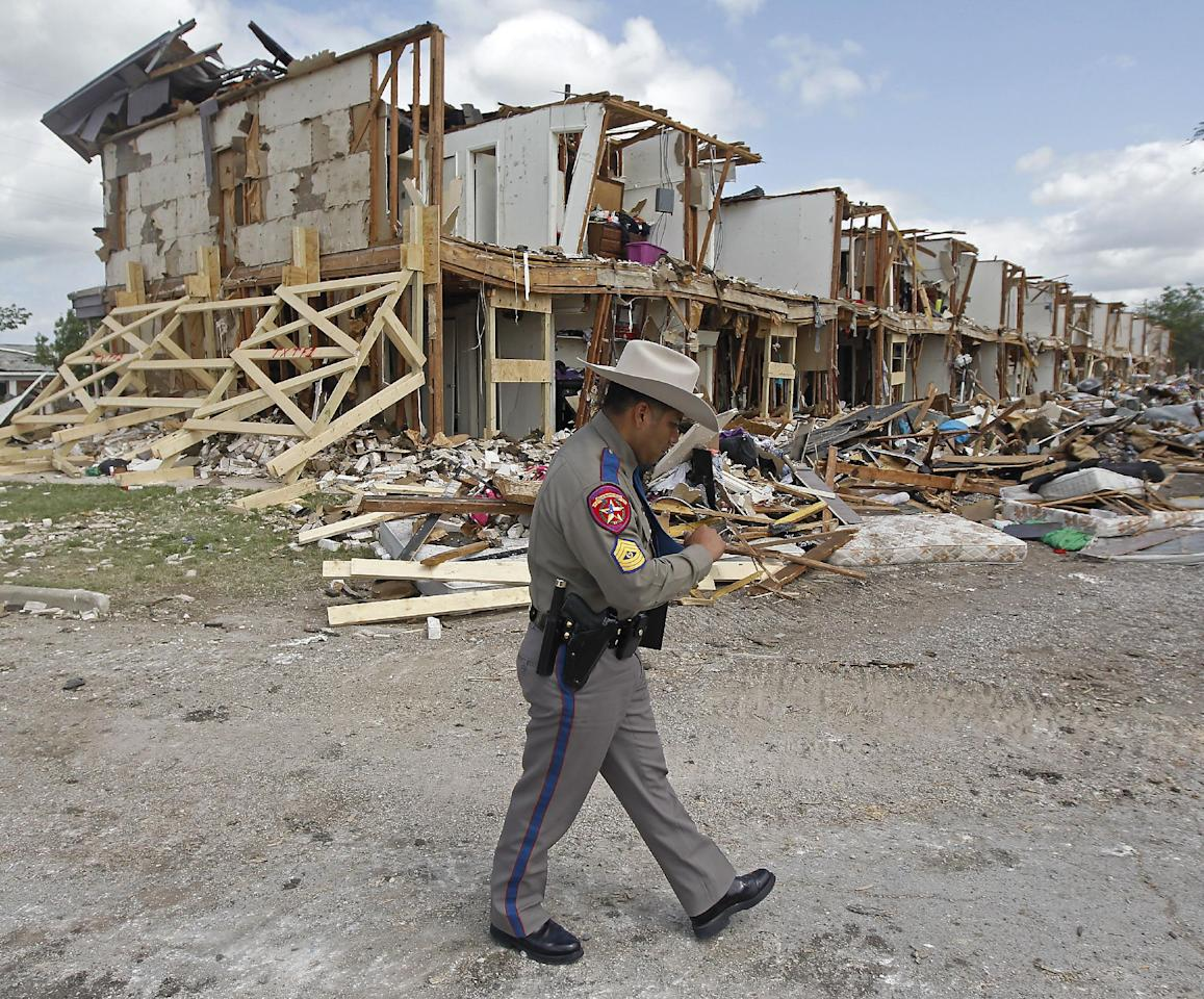 Texas Department of Public Safety Sgt. Jason Reyes walks past a damaged apartment complex, Sunday, April 21, 2013, four days after an explosion at a fertilizer plant in West, Texas. The massive explosion at the West Fertilizer Co. Wednesday night killed 14 people and injured more than 160. (AP Photo/The Dallas Morning News, Michael Ainsworth, Pool)