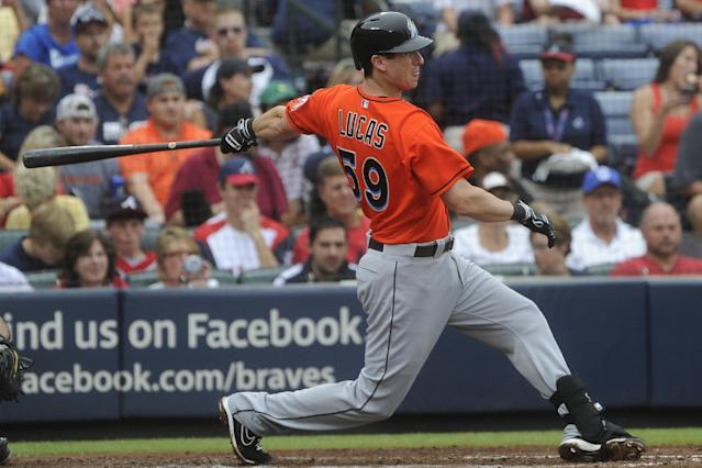Miami Marlins' Ed Lucas bats a two-run single line drive to centerfield during the third inning of a baseball game against the Atlanta Braves, Sunday, Sept. 1, 2013, in Atlanta. (AP Photo/John Amis)