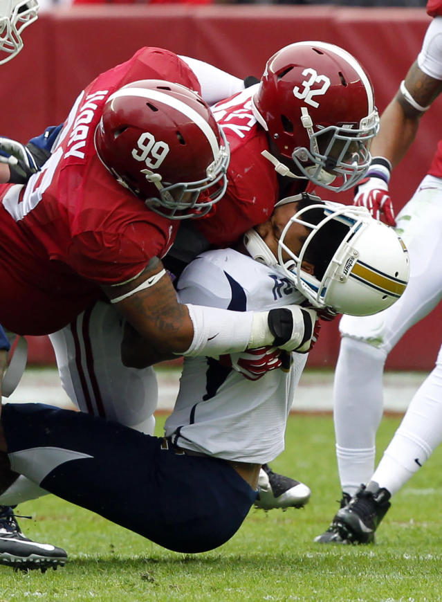 Alabama defensive lineman Brandon Ivory (99) and linebacker C.J. Mosley (32) tackle Chattanooga quarterback Terrell Robinson (6) knocking his helmet off during the first half of an NCAA college football game on Saturday, Nov. 23, 2012, in Tuscaloosa, Ala. (AP Photo/Butch Dill)