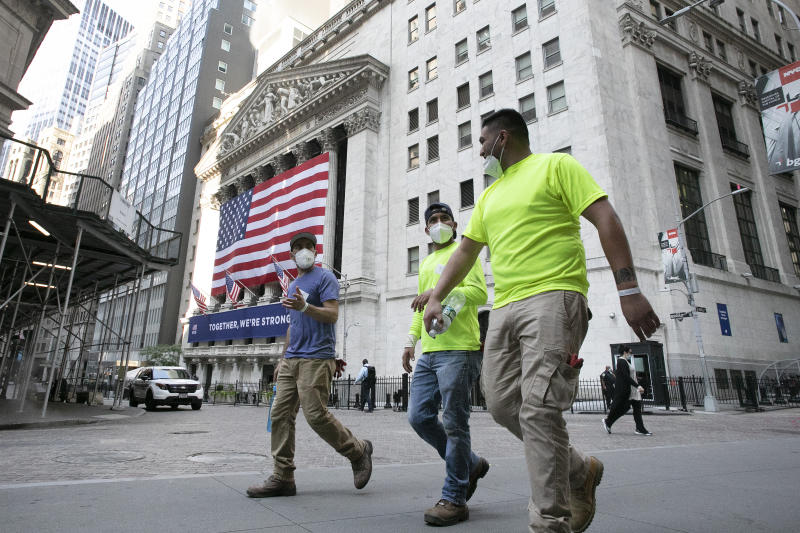 Workers wearing masks walk by the New York Stock Exchange during the coronavirus pandemic, Thursday, July 9, 2020, in New York. (AP Photo/Mark Lennihan)