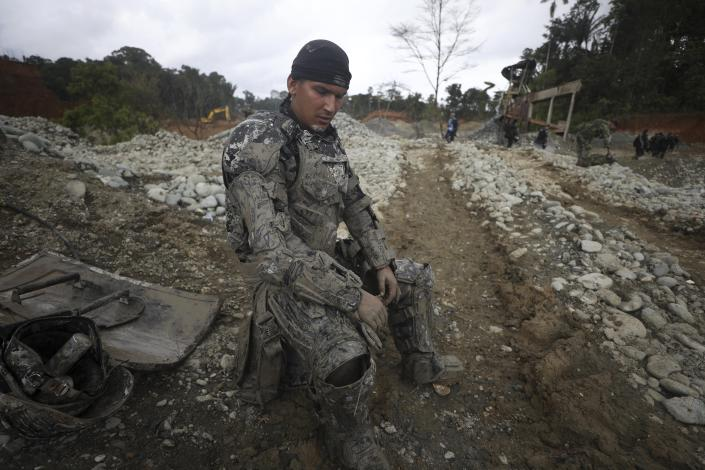 """Covered in mud, a National Police officer rests momentarily from destroying machinery at an illegal gold mine as part of the Armed Forces' """"Operation Guamuez III"""" in Magui Payan, Colombia, Tuesday, April 20, 2021. Illegal gold mining is common in Colombia, especially wildcat mines in poverty-stricken areas dominated by criminal gangs with little state presence. (AP Photo/Fernando Vergara)"""