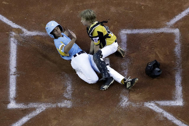 Wailuku, Hawaii's Nakea Kahalehau, left, scores under the tag by South Riding, Va.'s Noah Culpepper during the first inning of a baseball game at the Little League World Series in South Williamsport, Pa., Wednesday, Aug. 21, 2019. Hawaii won 12-9. (AP Photo/Gene J. Puskar)