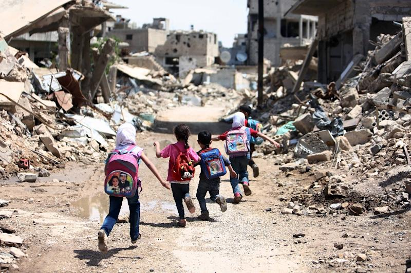 Syrian schoolchildren run past damaged buildings in the rebel-held are of Jobar, on the eastern outskirts of the capital Damascus, on April 30, 2016 (AFP Photo/Amer Almohibany)