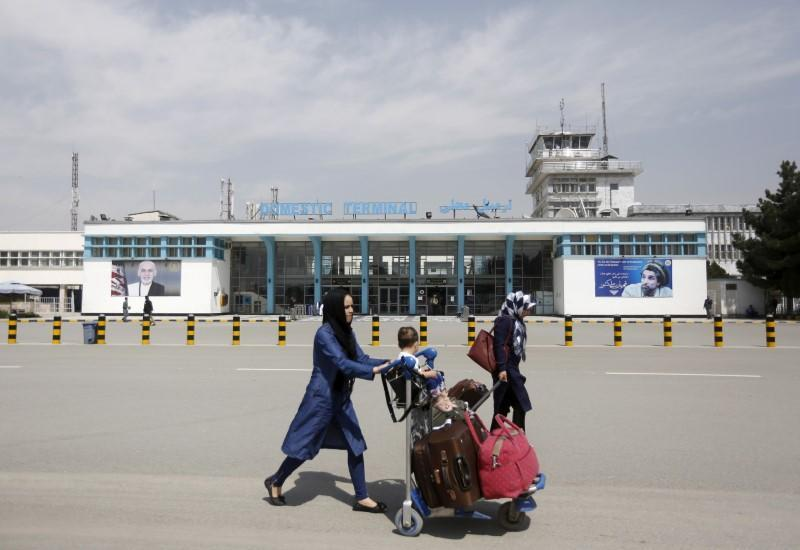 FILE PHOTO: Afghan passengers walk in front of Hamid Karzai International Airport in Kabul