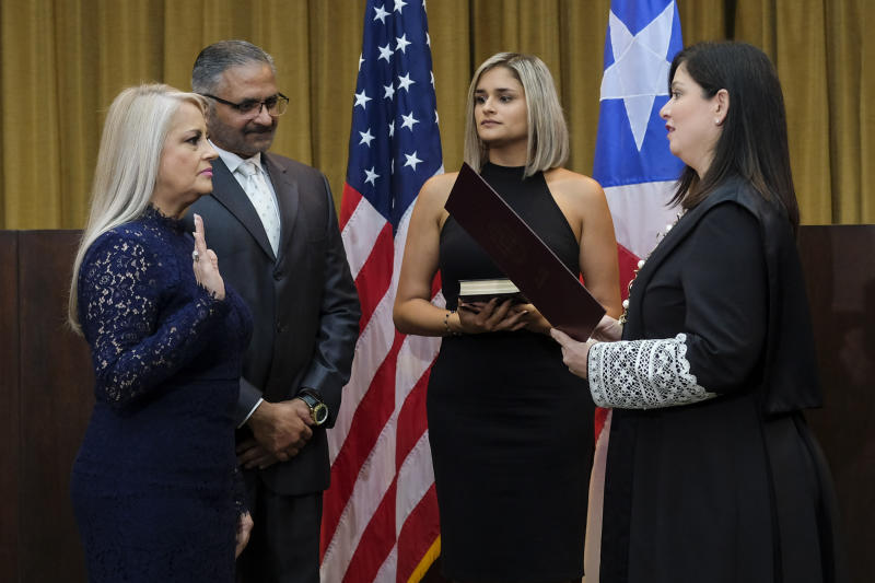 Justice Secretary Wanda Vazquez is sworn in as governor of Puerto Rico by Supreme Court Justice Maite Oronoz, in San Juan, Puerto Rico, Wednesday, Aug. 7, 2019. Vazquez took the oath of office early Wednesday evening at the Puerto Rican Supreme Court, which earlier in the day ruled that Pedro Pierluisi's swearing in last week was unconstitutional. Vazquez was joined by her daughter Beatriz Diaz Vazquez and her husband Judge Jorge Diaz. (AP Photo/Dennis M. Rivera Pichardo)