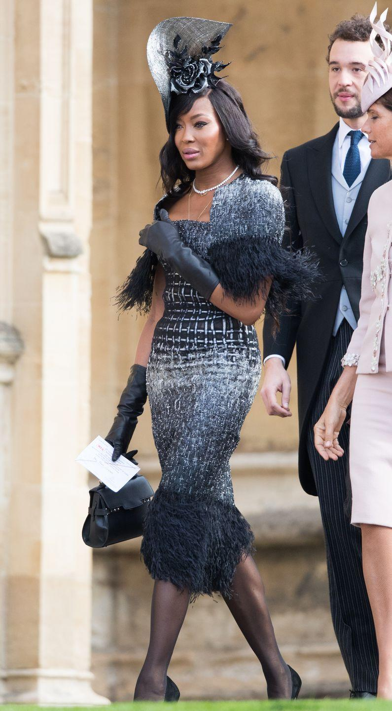 <p>Naomi Campbell's look at Princess Eugenie's wedding was flawless, including sleek leather gloves, a feather trim dress and gothic floral headpiece. </p>