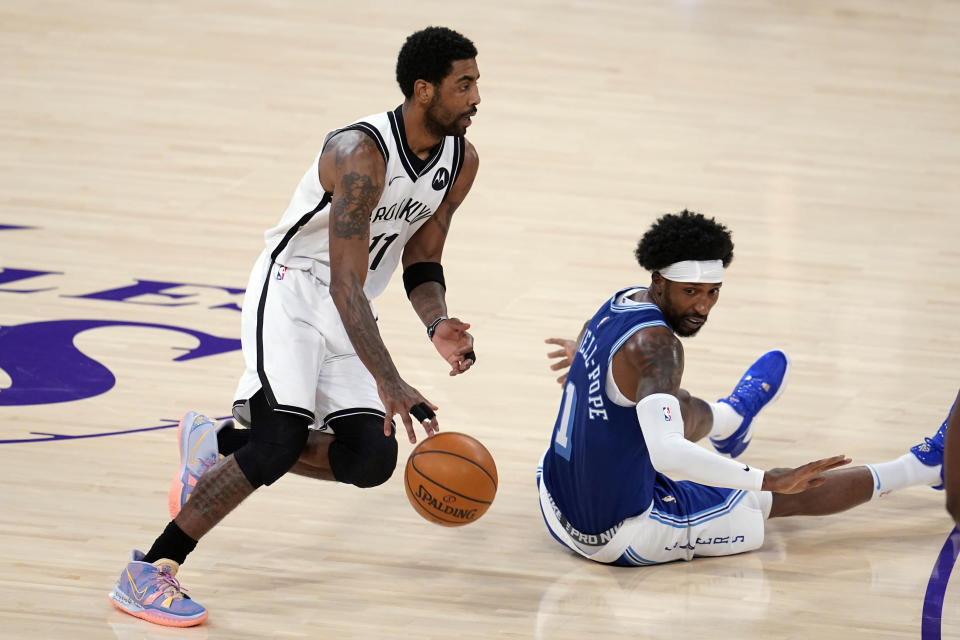 Brooklyn Nets guard Kyrie Irving, left, dribbles past Los Angeles Lakers guard Kentavious Caldwell-Pope during the first half of an NBA basketball game Thursday, Feb. 18, 2021, in Los Angeles. (AP Photo/Marcio Jose Sanchez)