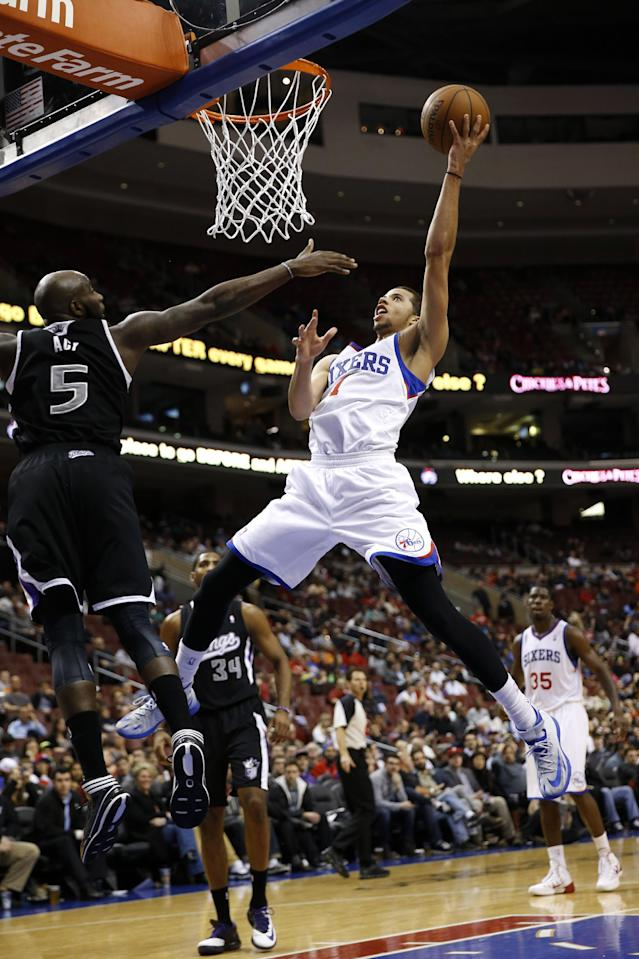 Philadelphia 76ers's Michael Carter-Williams, front right, goes up to shoot against Sacramento Kings's Quincy Acy during the second half of an NBA basketball game on Wednesday, March 12, 2014, in Philadelphia. Sacramento won 115-98. (AP Photo/Matt Slocum)