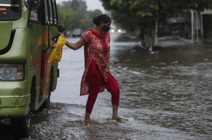 A woman alights from a bus at a flooded street during monsoon rains Jammu, India, Monday, July 12, 2021. India's monsoon season runs from June to September. (AP Photo/Channi Anand)
