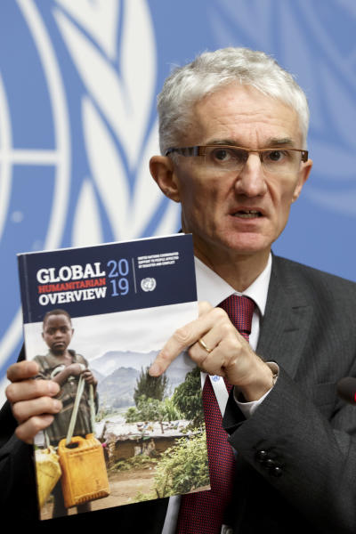 "Mark Lowcock, UN Under-Secretary-General for Humanitarian Affairs and Emergency Relief Coordinator, holds a report during a press conference about the launch of the ""Global Humanitarian Overview 2019"" and ""World Humanitarian Data and Trends 2018"" flagship reports, at the European headquarters of the United Nations in Geneva, Switzerland, Tuesday, Dec 4, 2018. (Salvatore Di Nolfi/Keystone via AP)"