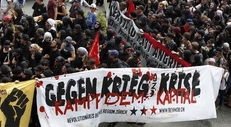 Anti-G7 protestors march during a demonstration in Garmisch-Partenkirchen, southern Germany, June 6, 2015. The Group of Seven (G7) two-day summit, being held at Elmau palace near Garmisch-Partenkirchen in Bavaria, begins on Sunday. The text reads 'Against war and crisis. Fight the capital.' REUTERS/Michaela Rehle