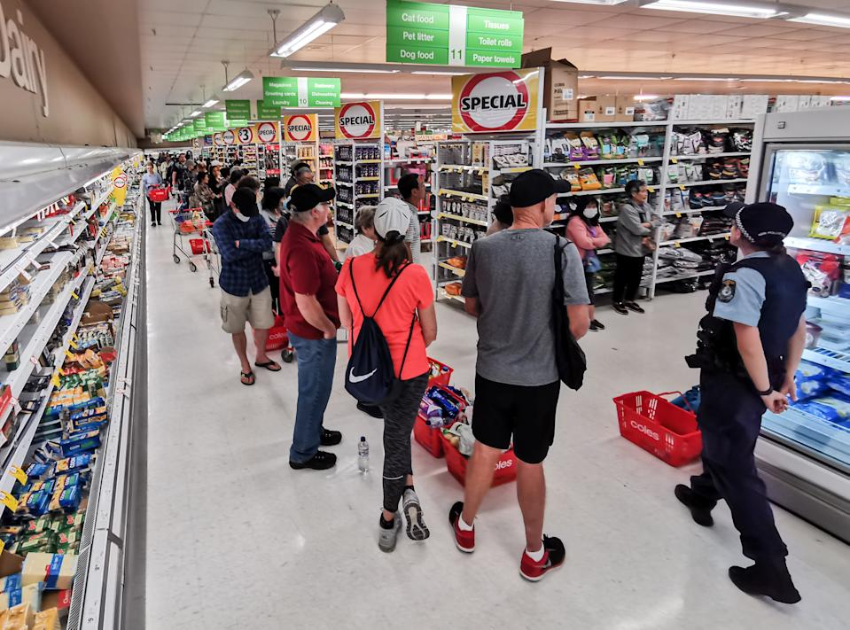A Police Officer watches on at people queueing for a delivery of toilet paper, paper towel and pasta at Coles Supermarket, Epping in Sydney, Friday, March 20, 2020. Supermarkets have been struggling to keep up with demand for products such as toilet paper in recent days, as panic buying as a result of the Covid-19 pandemic has resulted in people purchasing far more than usual. Supermarkets have put in place limits on the quantity people can purchase of many everyday items. (AAP Image/James Gourley) NO ARCHIVING
